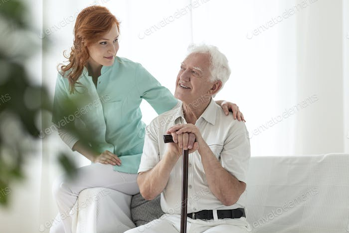 Friendly nurse and smiling elderly man with walking stick in the