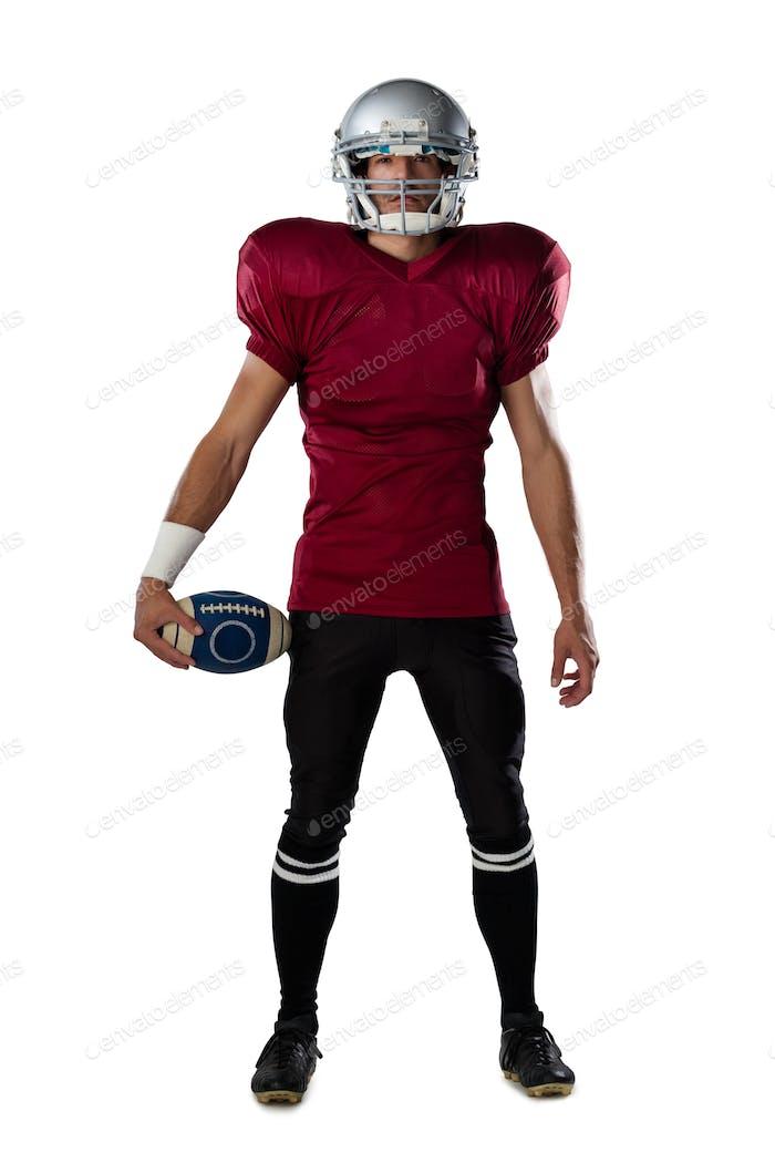 Full length of determined American football player wearing helmet