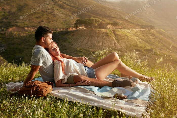 Couple relaxing at picnic on a summer day