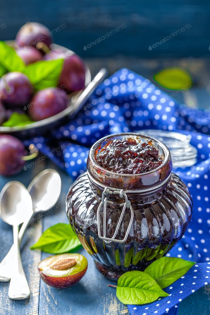 Plum jam in a glass jar and fresh fruits with leaves