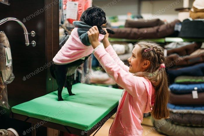 Маленькая девочка примерить одежду для щенка в зоомагазине
