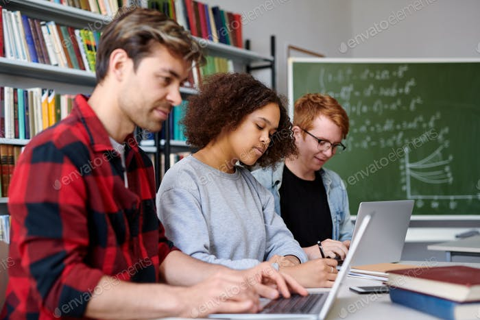 Three contemporary college students working individually