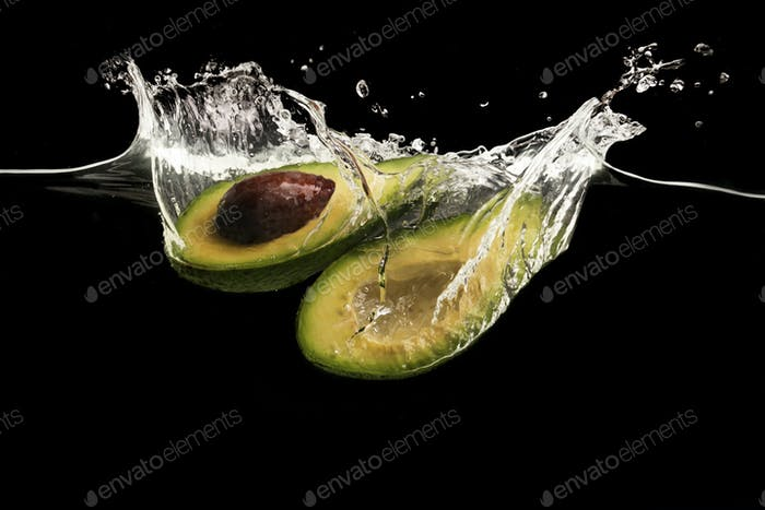 Avocado halves and water splashes on black background