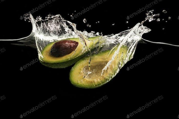 Avocado-Hälften und Wasserspritzer auf schwarzem Hintergrund