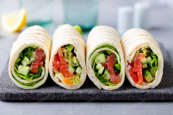 Wrap Sandwich, Roll with Fish Salmon and Vegetables on Cutting Board. Grey Background. Close up.