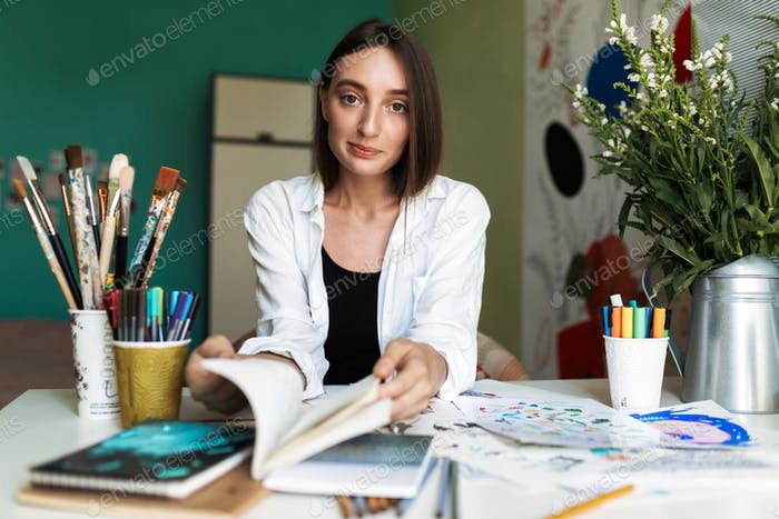 Pretty girl sitting at the desk with paintings dreamily looking