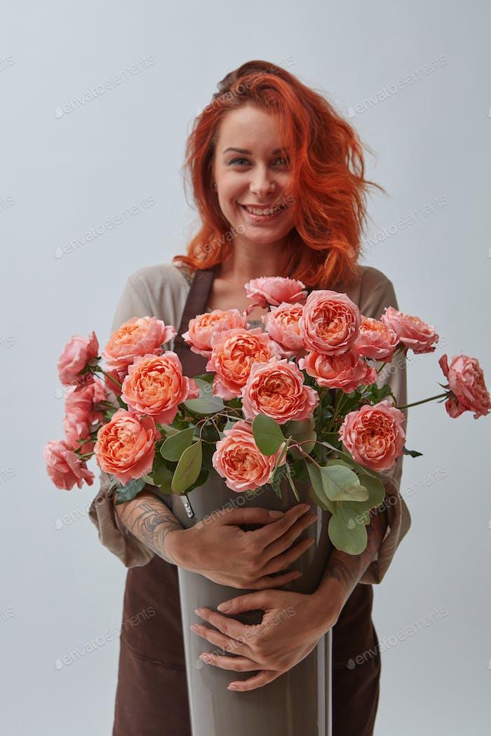 Junge Frau mit einer großen Vase von Rosen Blumen in einer Farbe des Jahres 2019 Living Coral Pantone auf einem