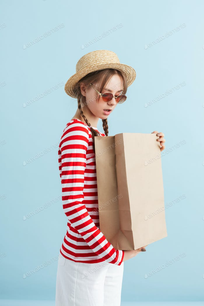 Young beautiful girl with two braids in straw hat and red sunglasses dreamily holding paper bag