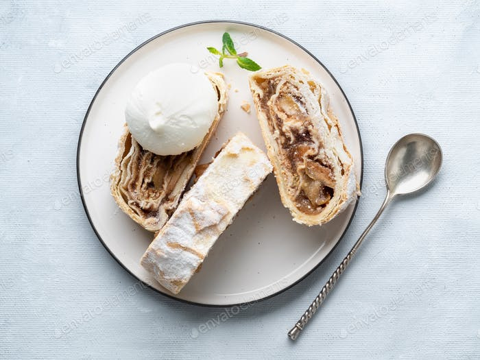 Apple strudel with ice cream and cinnamon. Baked cake, delicious dessert on the table. Top view