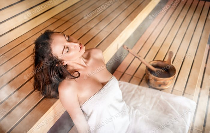 Young woman relaxing in sauna among hot steam