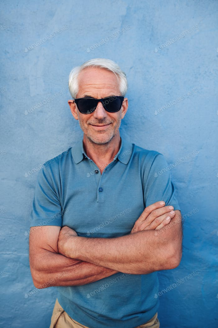 Handsome middle aged male posing against a blue wall