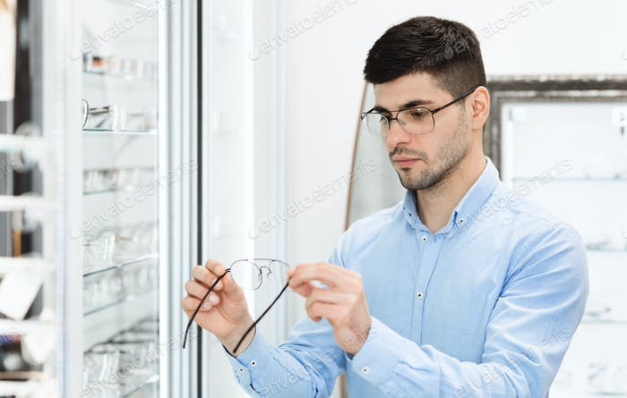 Portrait of serious young man choosing spectacles