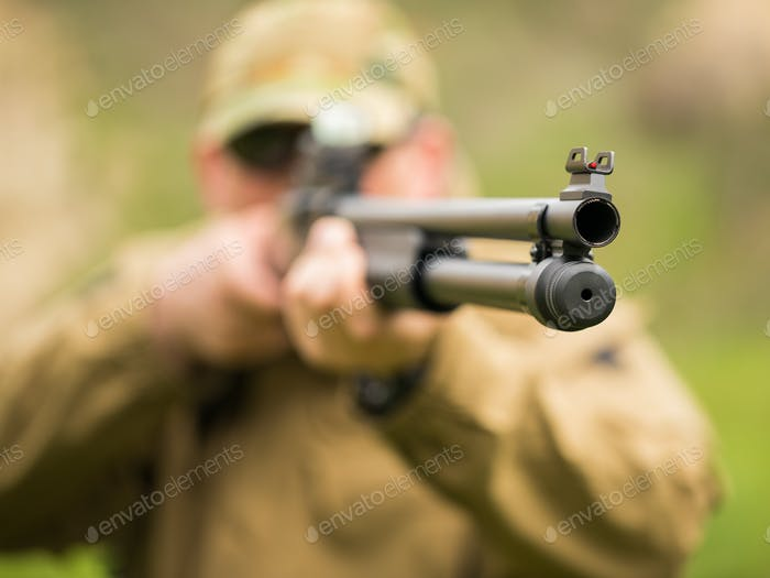 Man in camouflage with a shotgun aiming at a target