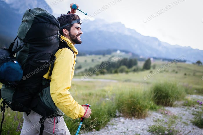 Hiker young man with backpack and trekking poles looking at the mountains in outdoor