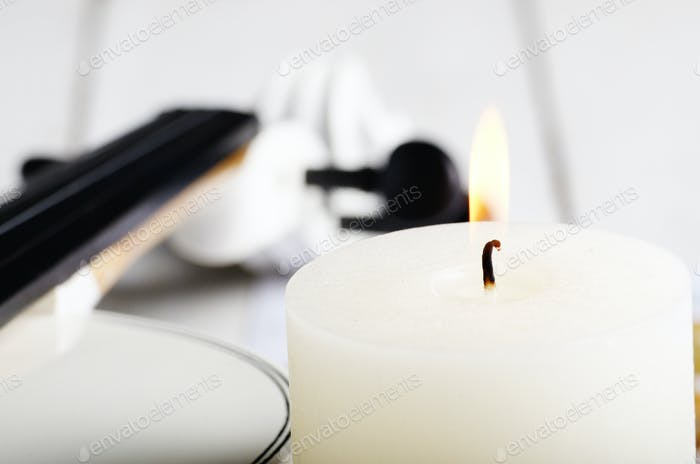 Close view of a candle and violin on wooden table