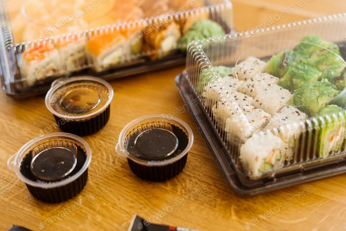 Sushi rolls delivery on wood background