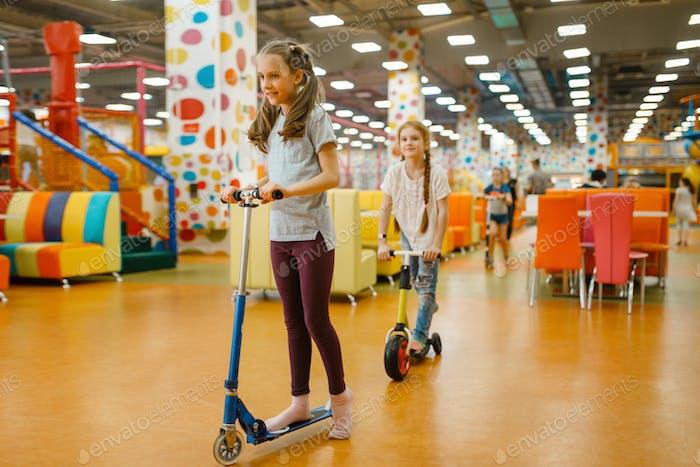 Kleine Freundinnen reitet auf Roller, Spielplatz