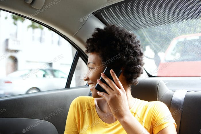 African woman on back seat of car making a phone call