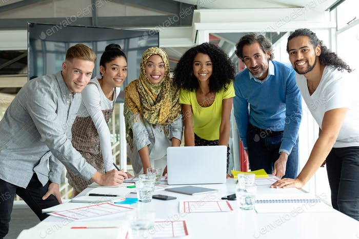 Diverse business people looking at camera while working together at conference room