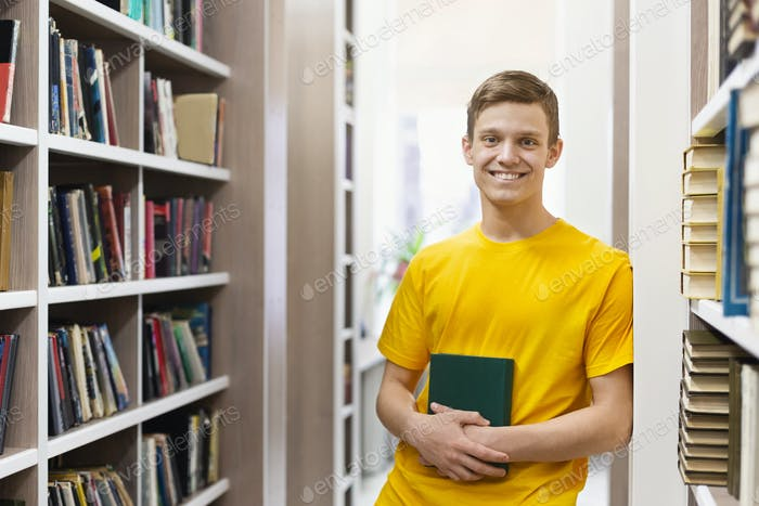 Happy guy student standing between bookshelves in library