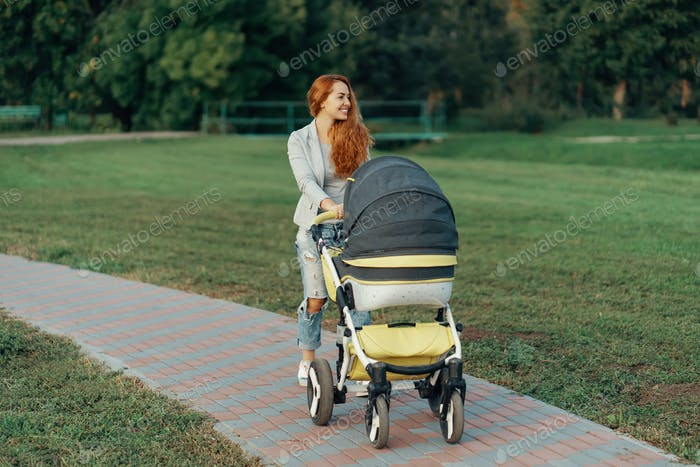 Mother enjoying walk carrying her little child in his baby troll