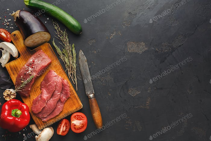 Raw beef filet mignon steaks on wooden board