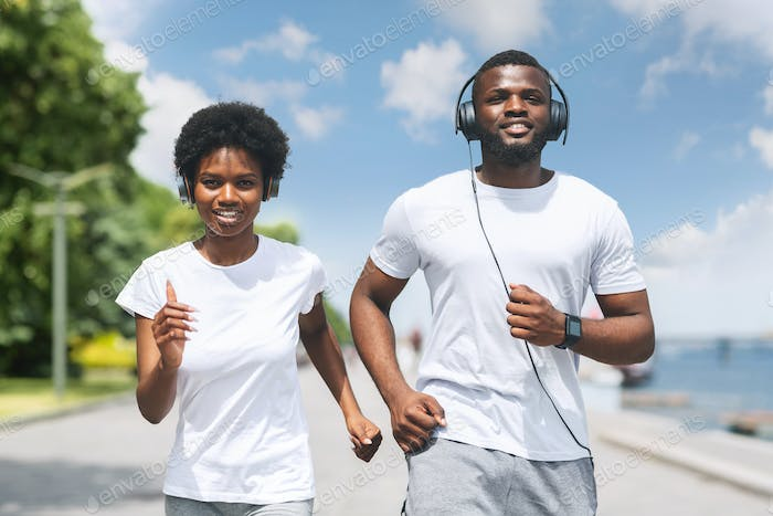 Smiling African American Couple Jogging Along River Bank In Morning