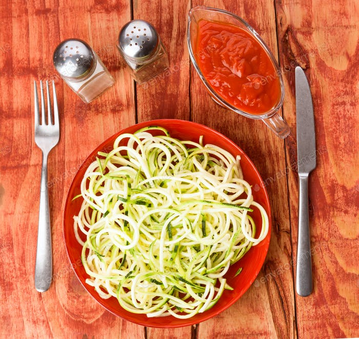 serving of raw zucchini spaghetti on wooden board