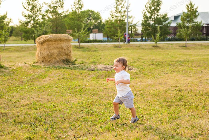 little boy playing in summer nature