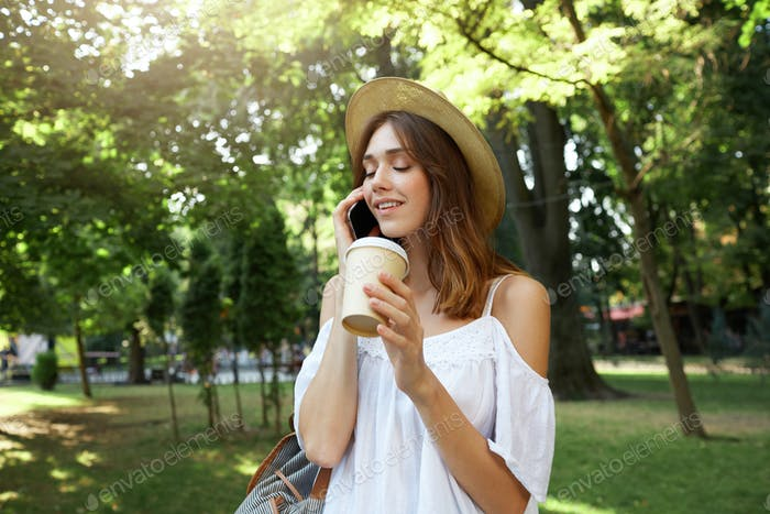 woman wears stylish summer hat and white dress, feels relaxed, smiling, talking on mobile phone