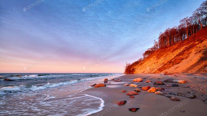 Puesta de  sol púrpura sobre una hermosa playa.
