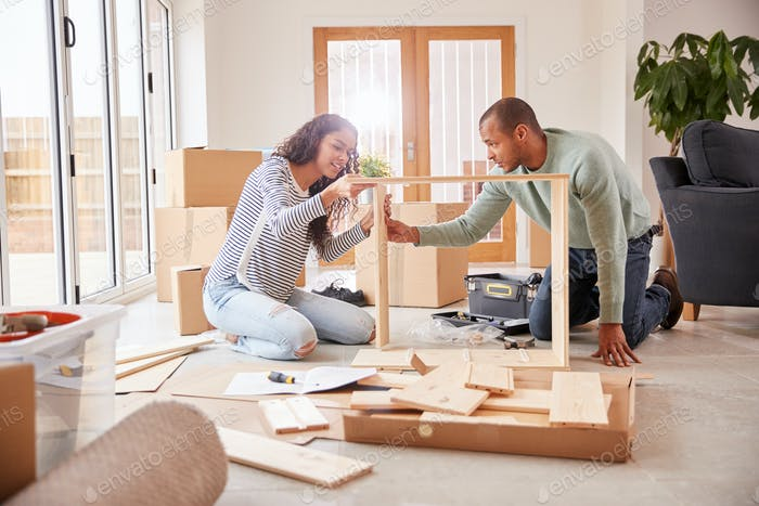 Couple In New Home On Moving Day Putting Together Self Assembly Furniture