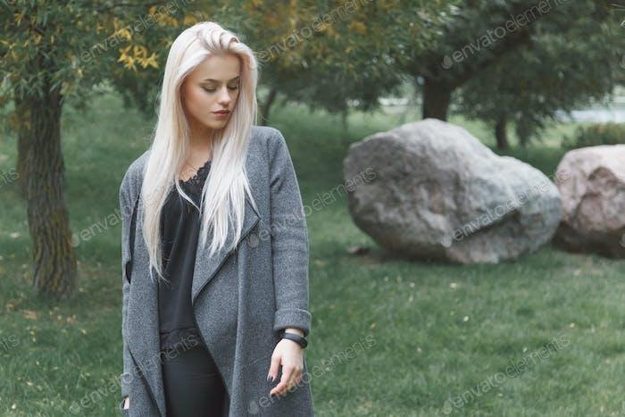 Junge blondhair Frau in einem grauen Mantel mit intelligenten Armband im Freien stehend.