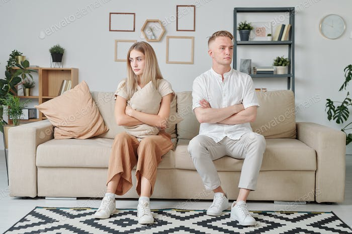 Young married couple with crossed arms and offended facial expression