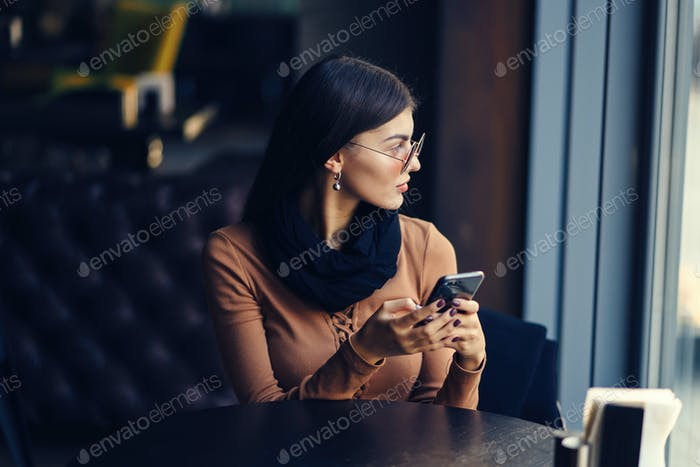brunette girl using phone while at a restaurant