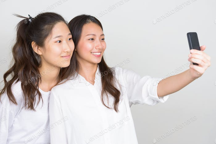 Two happy young beautiful Asian women as friends taking selfie together