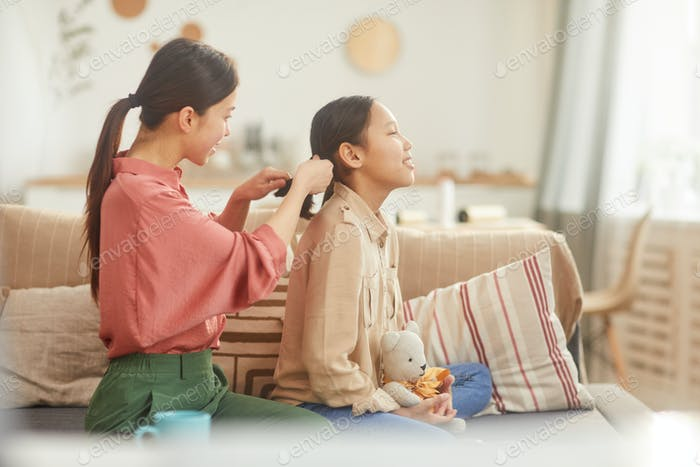 Mother Plaiting Girl's Hair