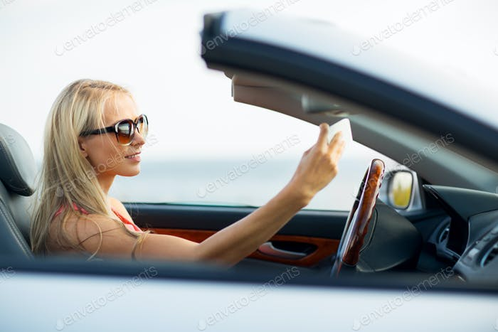 woman in convertible car taking selfie