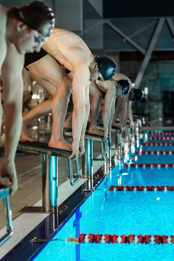 Men standing on starting blocks preparing