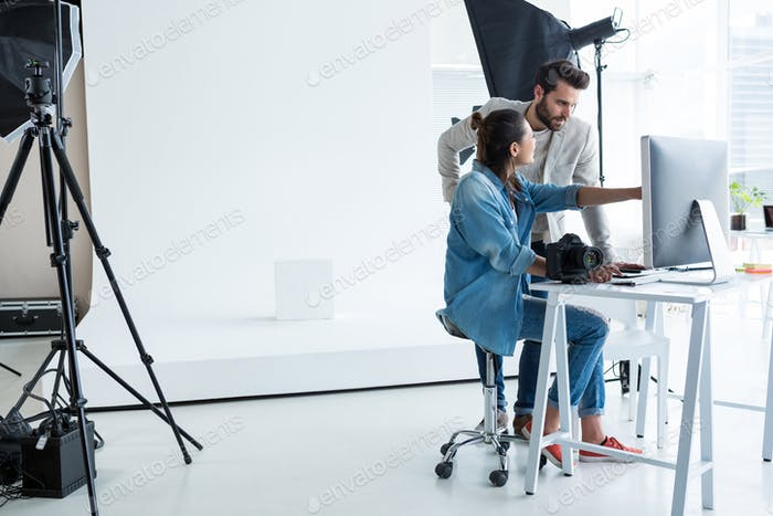 Photographers working together over computer