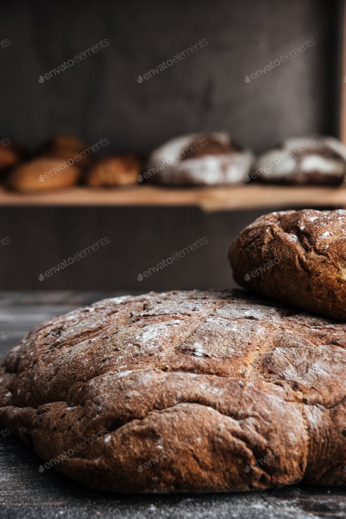 Bread with flour on dark wooden table at bakery