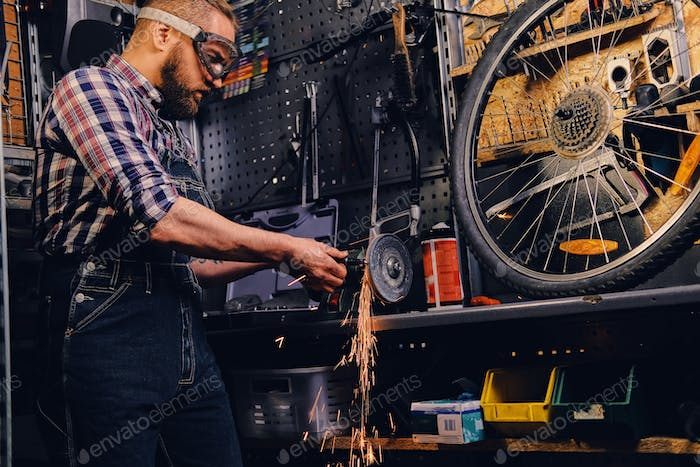 Mechanic cutting and polish bicycle part in a workshop.