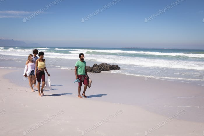 Front view of group of multi ethnic friends walking on the beach in the sunshine