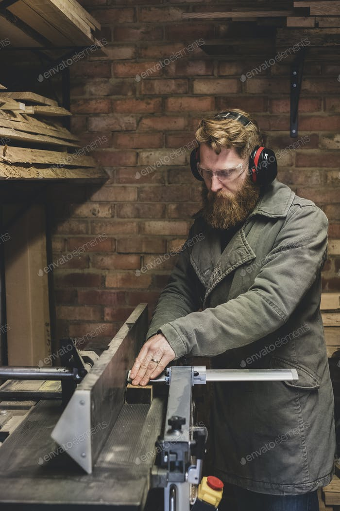 Bearded man standing in workshop, wearing ear protectors, working on piece of wood.
