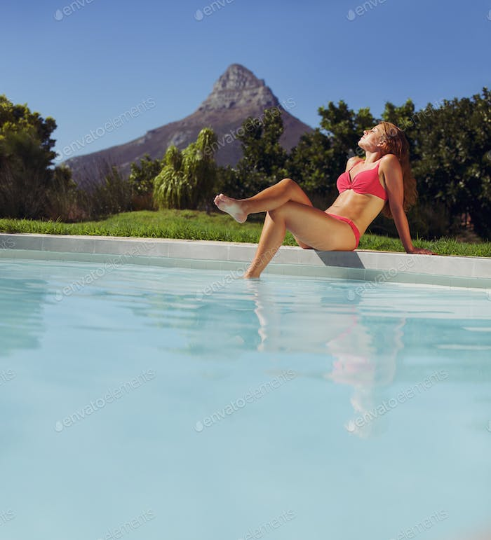 Young lady in bikini sunbathing by poolside