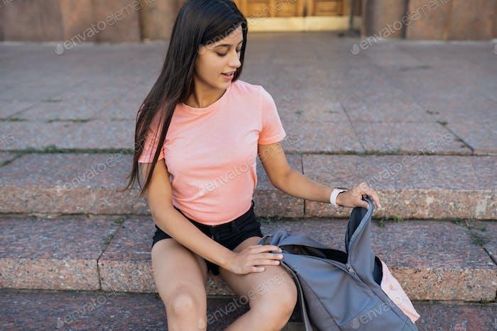 Mujer joven con mochila abierta en la calle