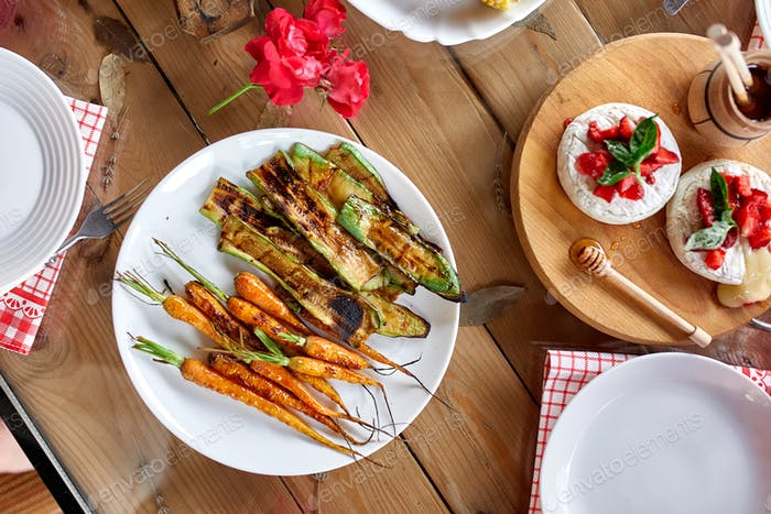 Dinner table with meat grill, roast vegetables, sauces and lemonade, variety serving
