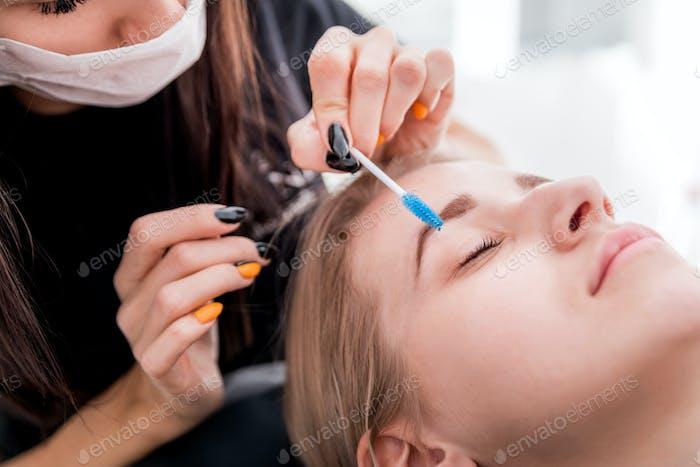 Pretty girl getting brow depilation at beauty salon