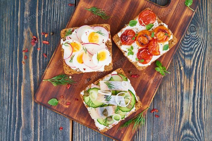 Smorrebrod - traditional Danish sandwiches. Black rye bread with fish, herring,