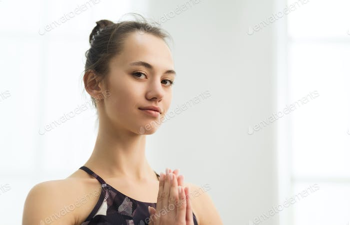 Beautiful woman practising yoga, holding hands in namaste